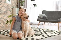 Cute little child with her pet on floor. At home stock photos