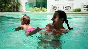 Cute little child and his mother having a swimming lesson in the pool. Mother holds in her hands on the background of stock video footage
