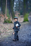 Cute little child, holding lantern and book in forest Stock Image