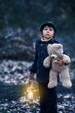 Cute little child, holding lantern and teddy bear in forest Stock Photos