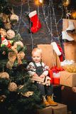 Cute little child opening present near Christmas tree. Merry Christmas and Happy New Year. Christmas dream for kids. stock photos