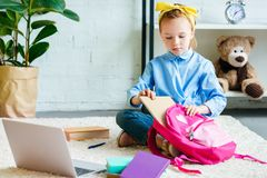 cute little child packing school bag while sitting on carpet stock photography