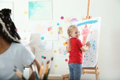 Cute little child painting on easel at lesson. Indoors stock image
