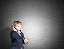 Cute little child on the phone near a chalkboard