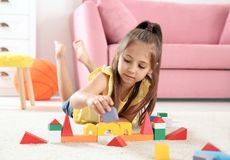 Cute little child playing with building blocks. On floor, indoors stock photos
