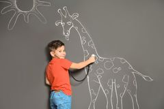 Cute little child playing doctor with chalk giraffe drawing on grey. Background royalty free stock photos
