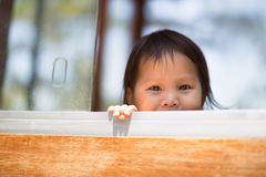Cute little child playing hide and seek in the park stock photo