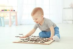 Cute little child playing with letters while sitting on floor royalty free stock photo