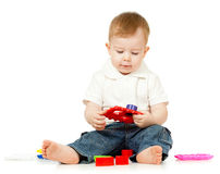 Cute little child is playing with toys while sitti. Child is playing with toys while sitting on floor, isolated over white Stock Images