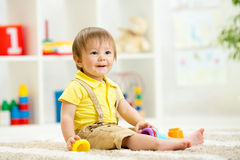 Cute little child is playing with toys while Stock Photography