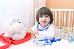 Cute little child plays doctor at home Stock Image