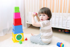 Cute little child plays educational toy at home. Cute 2 years boy plays educational toy at home Stock Photo