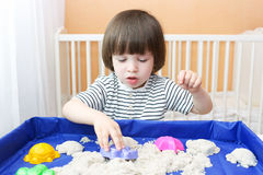 Cute little child plays kinetic sand Stock Photos
