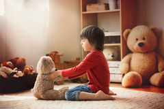 Cute little child, preschool boy, playing with teddy bear at home, having fun. Childhood happiness concept stock images
