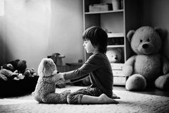 Cute little child, preschool boy, playing with teddy bear at hom royalty free stock photography