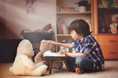 Cute little child, preschool boy, reading a book to his teddy be Royalty Free Stock Photos