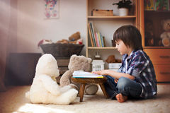 Cute little child, preschool boy, reading a book to his teddy be Royalty Free Stock Images