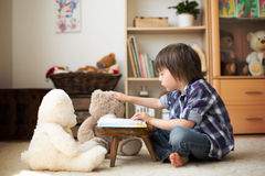 Cute little child, preschool boy, reading a book to his teddy be Royalty Free Stock Photography