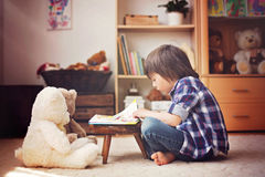 Cute little child, preschool boy, reading a book to his teddy be Stock Images