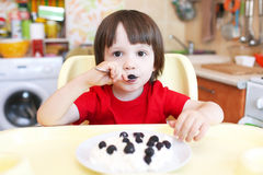 Cute little child in red t-shirt eats quark with berry on kitche Stock Photo