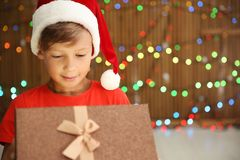 Cute little child in Santa hat opening Christmas gift box stock photos