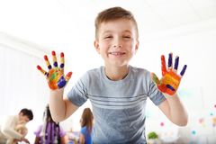 Cute little child showing painted hands at lesson royalty free stock images