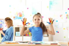 Cute little child showing painted hands at lesson royalty free stock photos