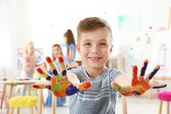 Cute little child showing painted hands at lesson royalty free stock image