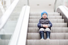 Cute little child sitting on moving staircase Stock Images