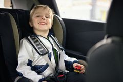 Cute little child sitting in safety car seat Royalty Free Stock Images