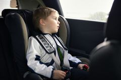 Cute little child sitting in safety car seat Stock Photo