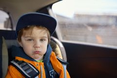 Cute little child sitting in safety car seat Stock Image