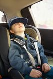Cute little child sitting in safety car seat and sleeps Stock Image