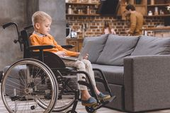Cute little child sitting in wheelchair and using laptop. At home stock photo