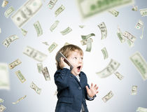 Cute little child with a smartphone under dollar rain Royalty Free Stock Photography