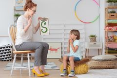 Child and teacher in kindergarten. Cute little child with speech impediment and smiling young preschool teacher learning the alphabet letters in kindergarten stock photos