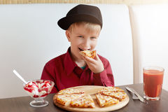 Cute little child in stylish clothes eating pizza and ice-cream drinking tomato juice while siting in cafe. Happy child eating del Stock Images