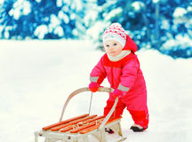 Cute little child walking with sled on snow in winter Royalty Free Stock Photos