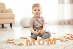 Cute little child and word MOM composed. Of wooden letters on floor at home stock photo