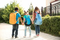 Cute little children with backpacks. Going to school Royalty Free Stock Photography