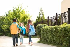 Cute little children with backpacks going. To school stock image