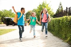 Cute little children with backpacks running outdoors. Elementary school Stock Images