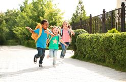 Cute little children with backpacks running. Outdoors. Elementary school stock photo