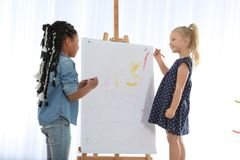Cute little children drawing on easel at painting lesson. Indoors stock photo