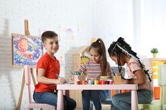 Cute little children drawing at painting lesson. Indoors stock photo