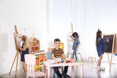 Cute little children drawing at painting lesson royalty free stock photos