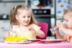 Cute little children drinking water at daycare. Or nursery stock photography