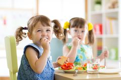 Cute little children eating food at daycare. Centre royalty free stock image