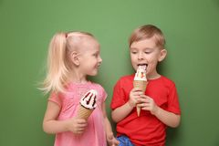 Cute little children eating ice cream on color  background. Cute little children eating ice cream on color background Stock Photo