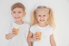 Cute little children eating ice cream on white  background. Cute little children eating ice cream on white background Royalty Free Stock Photo